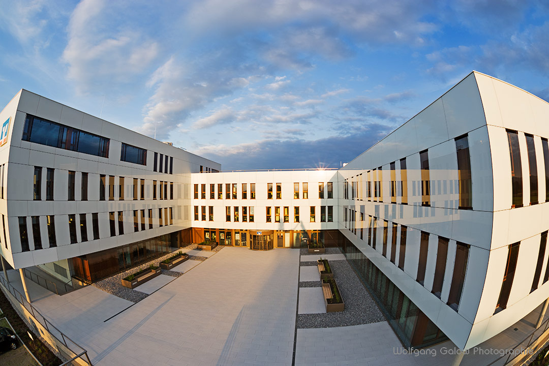 Das moderne Gebäude der Raiffeisenbank Bad Aibling - in den emaillierten Glassplatten, die das Gebäude vollständig verkleiden, spiegelt sich der blauweiße Himmel