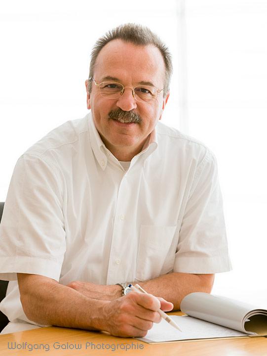 Foto im Hochformat: Ein Arzt in weißem Hemd an seinem Schreibtisch sitzend