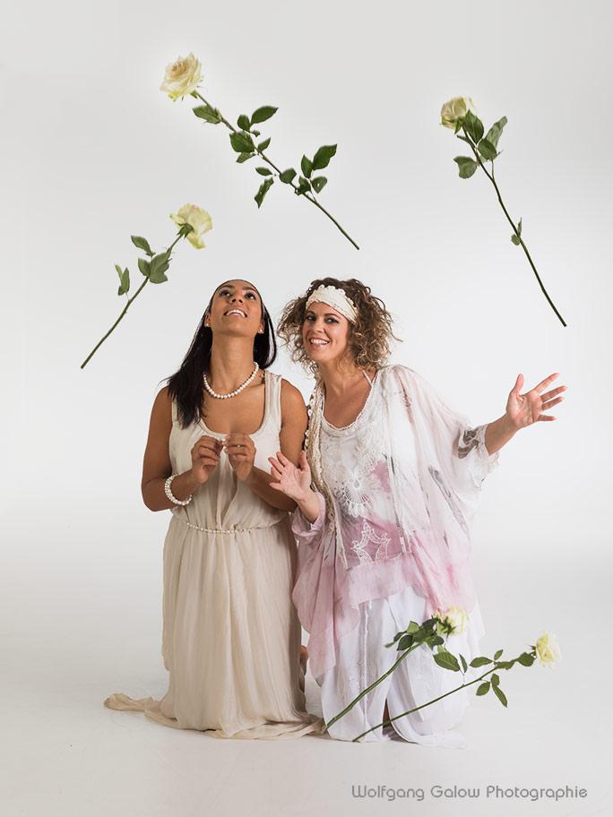 Bild in hellem Fotostudio von 2 Frauen in hellen Kleidern, auf dem Boden kniend und umgeben von fliegenden Rosen