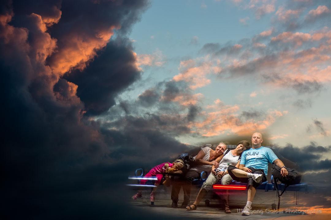 Farbfoto im Querformat: eine Fotomontage mit einer fünfköpfigen Familie auf einer Bank sitzend vor einem dramatischen Wolkenhimmel