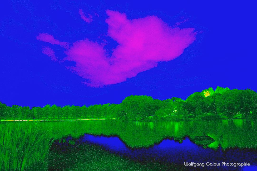 Farbfoto im Querformat: die Wolken schweben wie ein Geist in Purpur am dunkelblauen Himmel über Wald und See